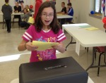 Erin Duffy drops her completed ballot in the ballot box during Miler Middle School's mock election.