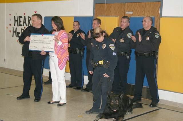 Hoglan Principal Amy Williams hands a check to Marshalltown Police Chief Mike Tupper for the penny war her school held in support of the MPD K-9 Unit.