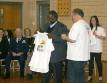 """John Johnson, Rogers Elementary parent and School Board member, presents Ralph Smith with a T-shirt from """"Spread the Words: Read by 3rd"""" the grade-level reading initiative in Marshalltown."""