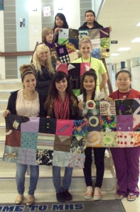 Some of the students from Fashion Design & Merchandising display their quilts before they're delivered to Iowa River Hospice.
