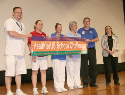 L to R: Food service employees Seth Ringgenberg, Wendy Mohler, Patty Martin, Calvin Scales and Vickie McVey hold up a banner presented to them by Ann Feilmann, Bureau Chief of the Iowa Department of Education Nutrition and Health Services.