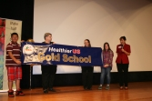 Bea Niblock, Vickie McVey, and a few Anson Elementary students display the banner presented to the school for receiving the HUSSC Gold Award.
