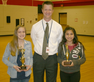 Spelling bee winner Abril Alcaraz (right) and runner-up Eve Nettesheim (left) with Principal Ralph Bryant.