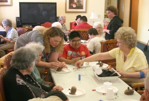Miguel Salas (center) and Wendy Beckman (standing, left) assist Bickford Cottage residents with crafts on May 14. Beckman's students visited Bickford monthly throughout the school year, completing crafts and playing games with residents.