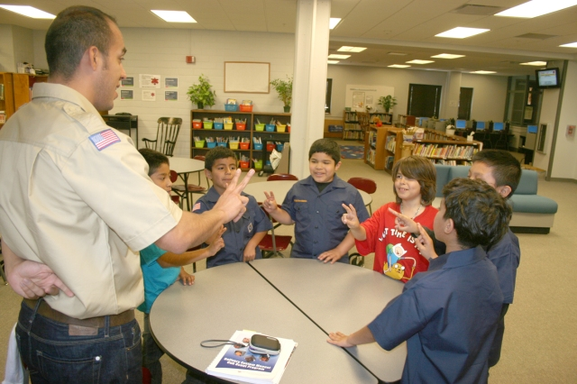 Scoutmaster Luis Ledesma leads members of Troop 1136 in reciting the Scout pledge.