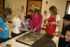 Muench works with Lenihan students on a mural for the school commons.