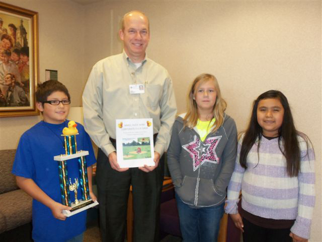Woodbury students present John Hughes, CEO of Marshalltown Medical & Surgical Center, with the Duck Dash First Place traveling trophy.  The duck representing MMSC placed first in the Woodbury Duck Dash – Corporate division held on Tuesday, Oct. 8.  MMSC provided sponsorship for the fundraising effort for new playground equipment.