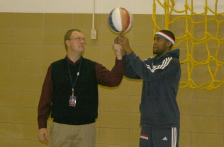 "Harlem Globetrotter Brawley ""Cheese"" Chisholm teaches Franklin Principal Tim Holmgren to spin a basketball on his finger during an assembly at the school Monday. Chisholm also visited Miller Middle School."