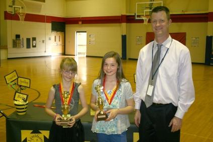 Spelling bee champions Jade Tesar (left) and Jillian Lang with Principal Ralph Bryant.