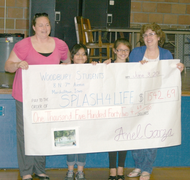 Jackie Ibarra and Isabella Pantoja present Leigh Bauder and Misty Smith with a check for $1,542.69 toward splash pads.