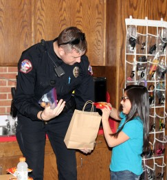 MPD Officer Eric Siemens accepts a gift from Anson Kindness Club students.